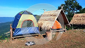 The camping blue/Green and orange tent on wooden litter with dry leaves roof and blue sky, mountain and tree