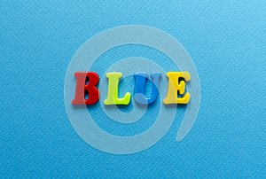 Word `blue` from plastic coloured magnet letters on blue paper b