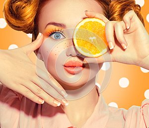 Beauty joyful teenage girl takes juicy oranges. Teen model girl with freckles, funny red hairstyle, yellow makeup and nails