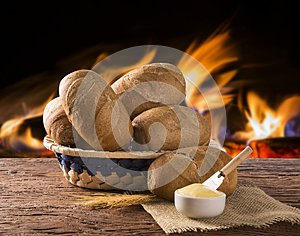 Basket of `French bread`, traditional Brazilian bread with butter on wood background