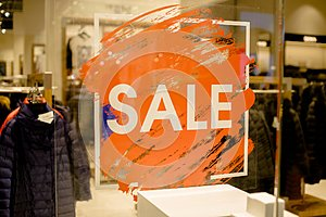 SALE Sign on the shop`s window display.discount sign on show window. Sale sign, symbol in clothes shop,The red