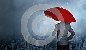 Businessman standing while holding an red umbrella over storm in huge rain background.