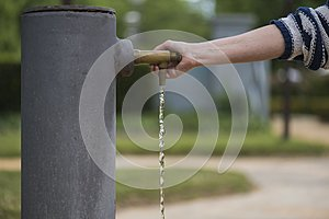Person opens the tap of the water fountain