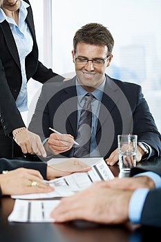Smiling executive signing contract