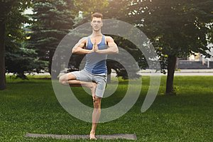 Young man training yoga in tree pose outdoors