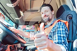 Truck driver sitting in cabin giving thumbs-up