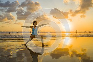 Young fit and attractive sport woman in beach sunset yoga practice workout on wet sun in front of the sea in meditation and relaxa