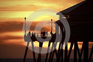 Orange sunset sky with silhouettes of people and the Huntington Beach Pier