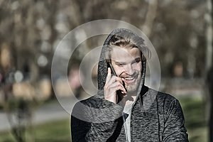 Fashion macho smiling with smartphone in casual sweatshirt. Happy guy in hood talk on mobile phone on sunny outdoor. Bearded man s