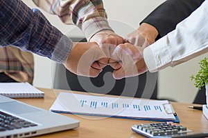 Close-up of business partners making pile of hands at meeting,Team work