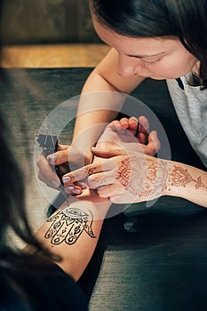 Artist applying henna mehndi tattoo on female hand