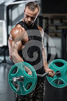 Muscular man working out in gym doing exercises with barbell at biceps, strong male bodybuilder