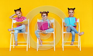 Funny children girls read books on a colored yellow background