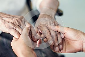 Close up hands of helping hands for elderly home care.