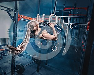 Concept: power, strength, healthy lifestyle, sport. Powerful attractive muscular woman at CrossFit gym