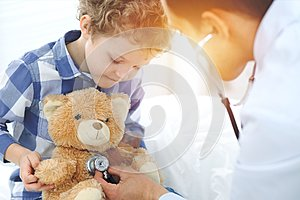 Doctor and child patient. Physician examines little boy by stethoscope. Medicine and children`s therapy concept