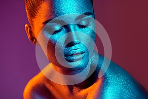 Fashion model woman in colorful bright sparkles and neon lights posing in studio, portrait of beautiful girl