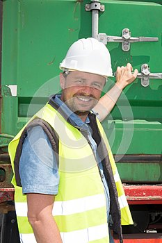 smiling man on a construction site opens a container truck