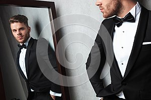 Mirror reflection of relaxed young man wearing a black tuxedo