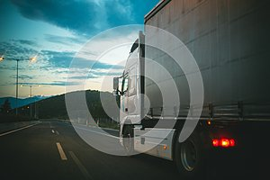 Lorry car drive on road in evening. Truck transport cargo. Transportation and shipment. Speed and delivery concept