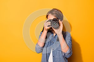 Close up photo of female photographer photographing with a camera in casual clothes on the bright yellow background