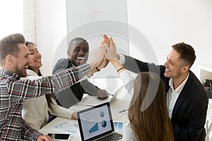 Excited millennial group giving high five for result achievement