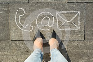 Female feet with contact symbols phone mail and letter, written on grey sidewalk, communication or contact us concept.