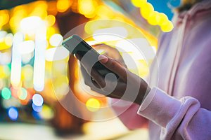 Girl pointing finger on screen smartphone on background bokeh light in night atmospheric city illumination in evening street defoc