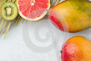 Tropical Nature Background Ripe Juicy Red Mango Slices of Grapefruit Kiwi Spiky Green Yellowish Palm Leaf. Healthy Food Lifestyle