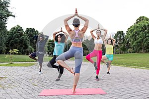 Yoga classes outdoors with multiracial group in different physic