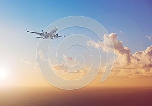 Airplane flying above ocean with sunset sky background - trav