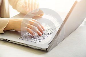 Woman working on computer close up. Woman hands typing on keyboard of laptop, online shopping detail. Business, remote