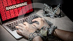 Locked hands and ransomware cyber attack on laptop