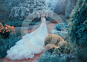 Blonde, with a beautiful elegant hairdo, walks in a fabulous blooming garden. Princess in a luxurious light pink dress