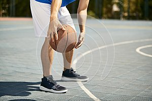 Young asian male basketball player practicing dribbling