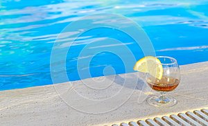 Blue pool water, a glass of flavored cognac with a slice of lemon at the water`s edge