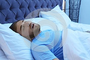 Young man snoring while sleeping in bed at night
