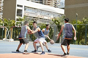 Young asian men playing basketball
