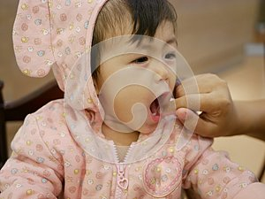 Little Asian baby girl opens her mouth to let her mother check her two new emerging teeth