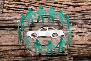 Green Paper Team Surrounding Car On Wooden Table
