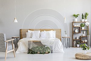 Patterned armchair near white wooden bed in grey bedroom interior with pouf and plants. Real photo