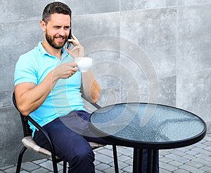 Coffee break brings physical and mental wellbeing. Man sit terrace and drink cappuccino speak phone grey wall background