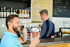 Confident entrepreneur choose drink in paper cup to go while communicate mobile. Man speak mobile phone and drink coffee