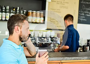 Guy busy speak phone while relax coffee break. Ready to hear you. Man holds cup of drink while have mobile conversation