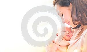 Mother and her newborn baby together. Happy mother and baby kissing and hugging. Maternity concept