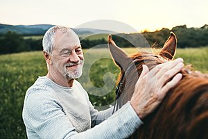 A senior man standing close to a horse outdoors in nature, stroking it.