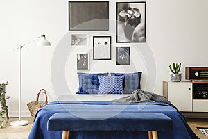 Bench in front of bed with navy blue pillows between lamp and cabinet in bedroom interior. Real photo