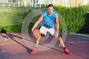 Young man athlete on basketball court dribbling