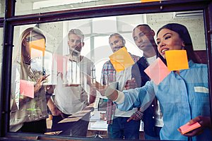 Business people meeting at office and use post it notes to share idea. Brainstorming concept. Sticky note on glass wall