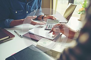 Calculate budget and business planning concept, two people couting revenue and expenditure by using calculator and looking paper